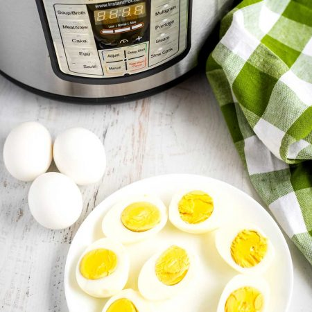 Hard-boiled eggs on a plate with an Instant Pot in the background