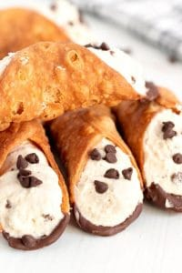 Cannolis stacked on top of each other.