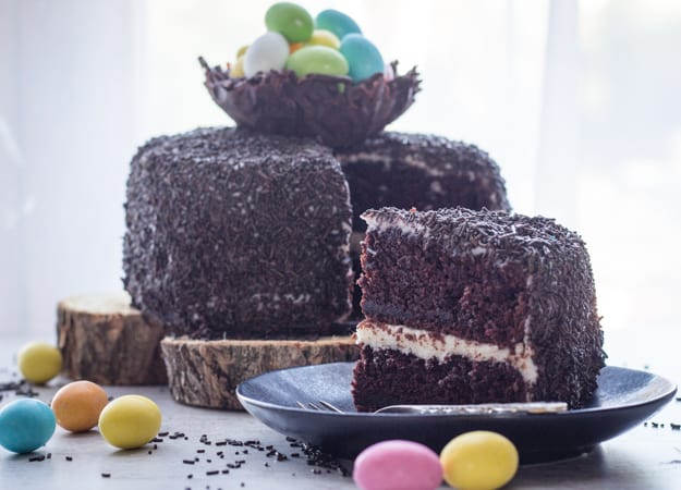 A piece of Chocolate Easter Egg Nest Cake on a plate with the rest of the cake on a serving platter in the background