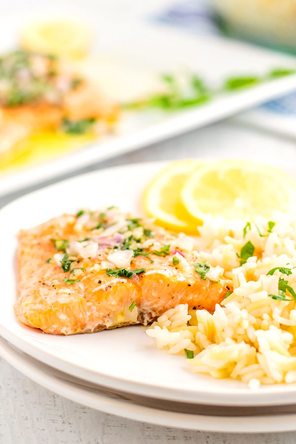 Salmon fillet on a white plate that's topped with lemon vinaigrette.