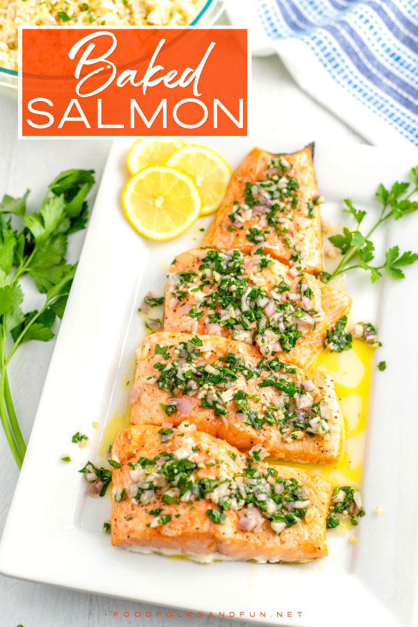 Overhead picture of baked salmon on a white platter with lemon slices and parsley.