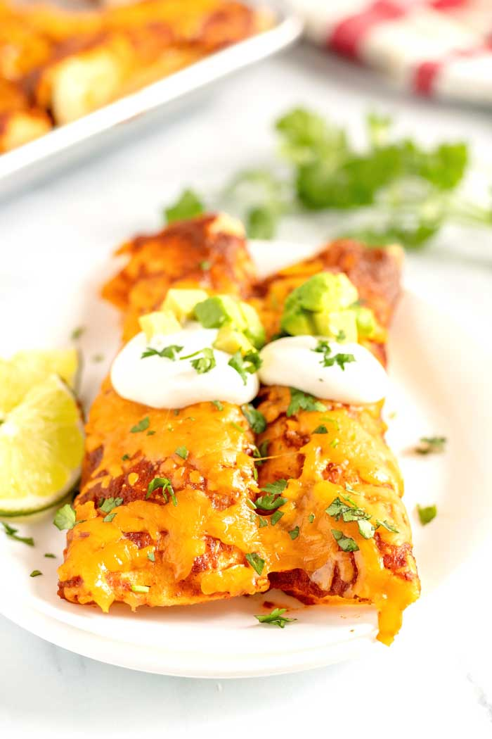 Shredded beef enchiladas on a plate topped with sour cream, avocado, and chopped cilantro.