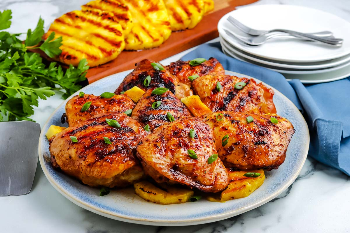 8 grilled chicken thighs on a serving platter.
