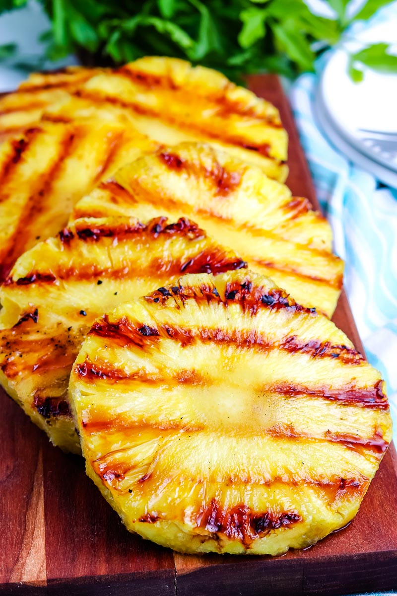A close up picture of Grilled Pineapple on a wooden serving platter.
