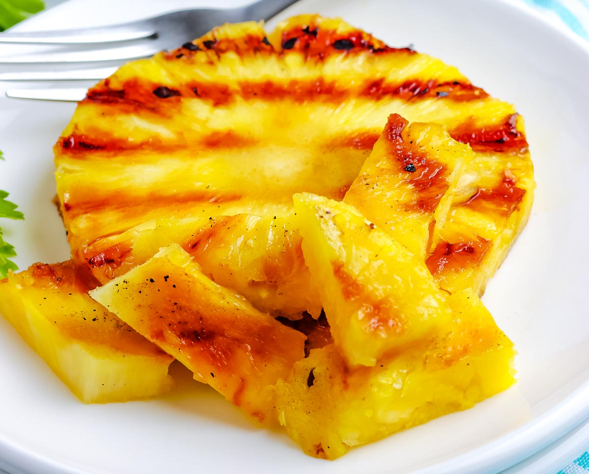 A close up picture of Grilled Pineapple cut up into bite-sized pieces.