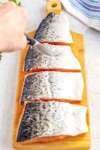 On the skin of each piece of salmon, make 4 shallow cuts, making sure to not cut into the pink part of the salmon.