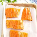 Use a couple pieces of paper towels to pat the salmon fillets dry. Then, rub each fillet with 1 teaspoon of olive oil and season with salt and black pepper.