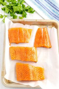 Process shot for salmon fillets on a baking sheet