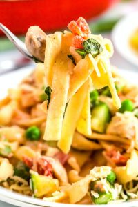 A close up picture of a fork listing up some Pasta Primavera