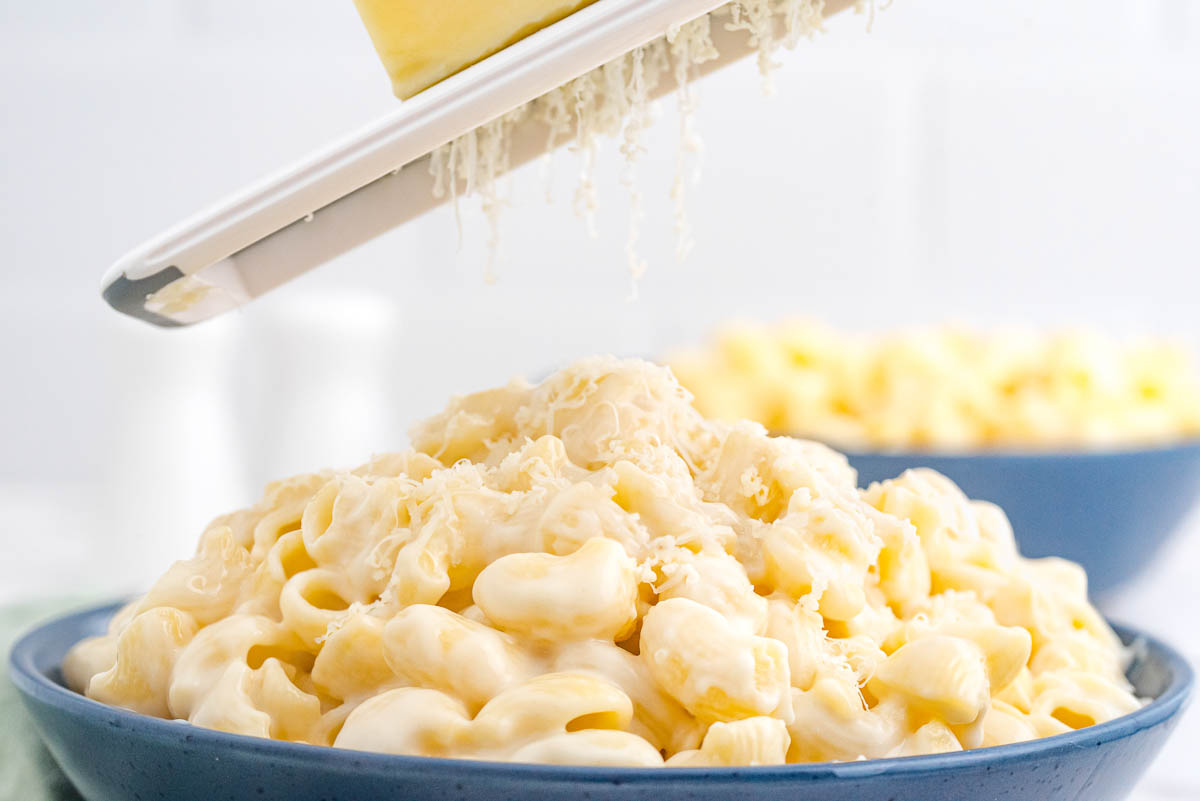 Cheese being grated on top of the finished Panera Mac and Cheese recipe.