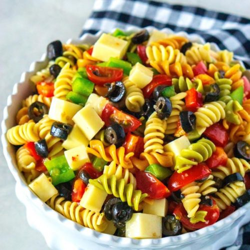 Pasta salad with lots of vegetables and cubbed cheese.