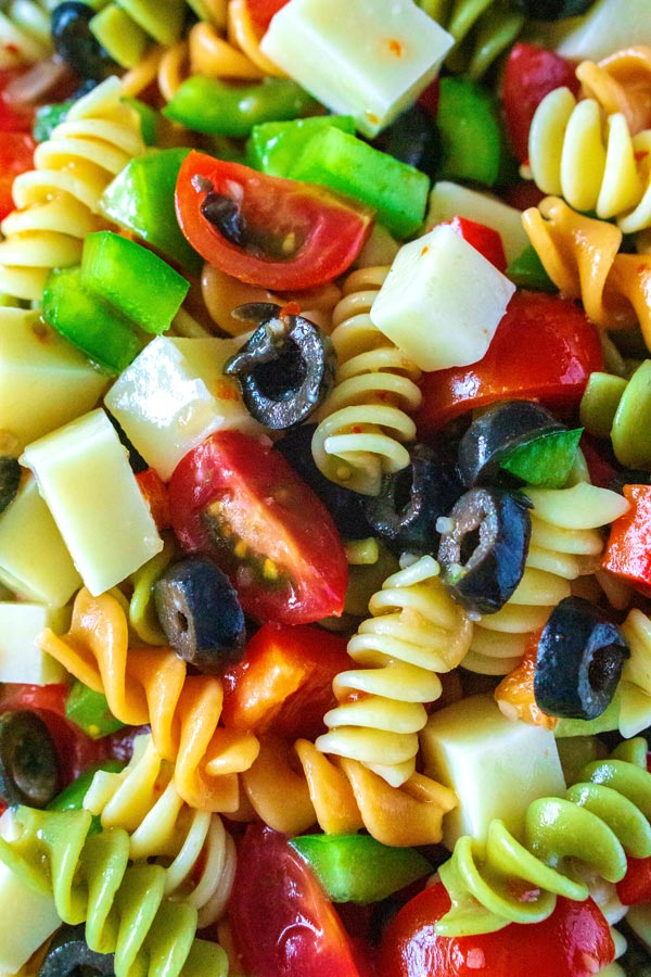 A closeup picture of pasta salad with Italian dressing.