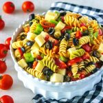 Pasta salad in a white bowl with a checkered napkin.
