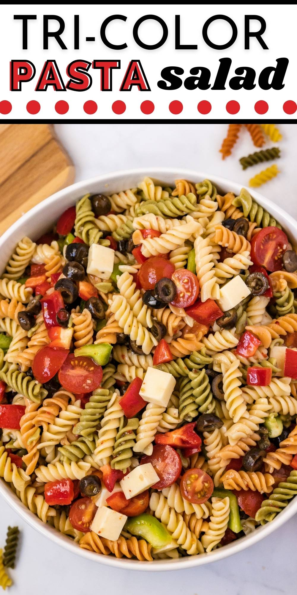 This Tri-Color Pasta Salad With Italian Dressing is made with rotini, Italian dressing, mozzarella cheese, bell peppers, black olives, and cherry tomatoes. via @foodfolksandfun