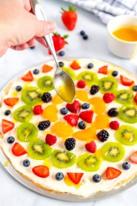 A spoon drizzling a glaze over the fruit pizza.