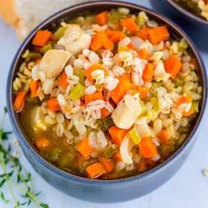 A close up picture oc the finished Chicken Barley Soup in a blue bowl.