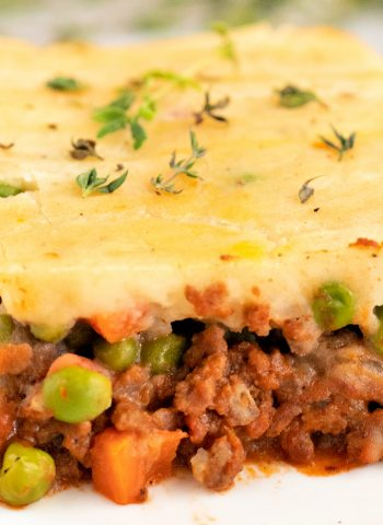 A close up picture of a slice of classic shepherd's pie recipe on a white plate.