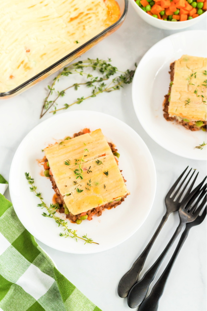 Pieces of shepherd's pie on white plates.