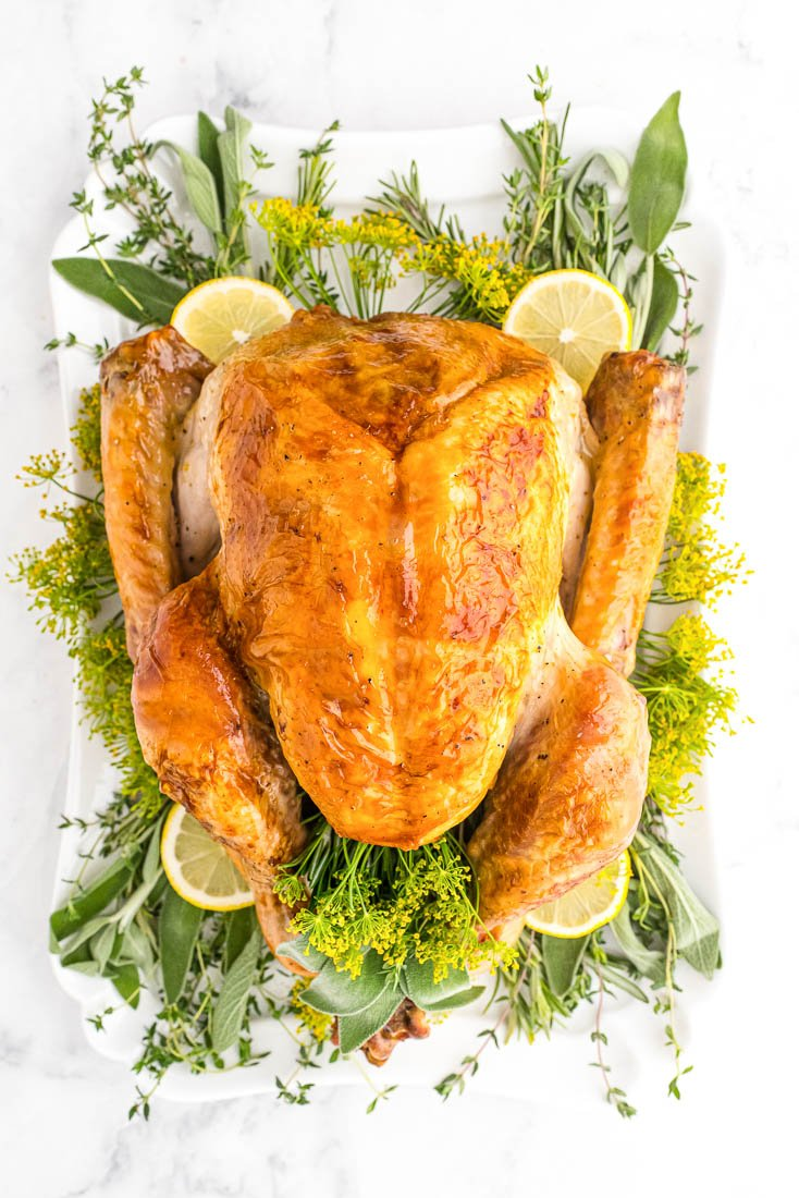 An overhead picture of the finished Oven Roasted Turkey recipe on a white platted surrounded by fresh herbs and lemon slices.