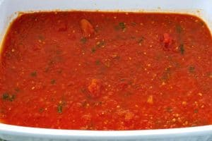 Pour sauce into the bottom of a 9x13-inch pan.