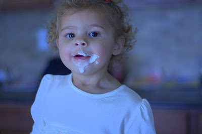 1-year-old helping with cream cheese frosting.