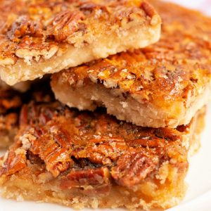 A close up of 3 pecan pie bars on top of each other.