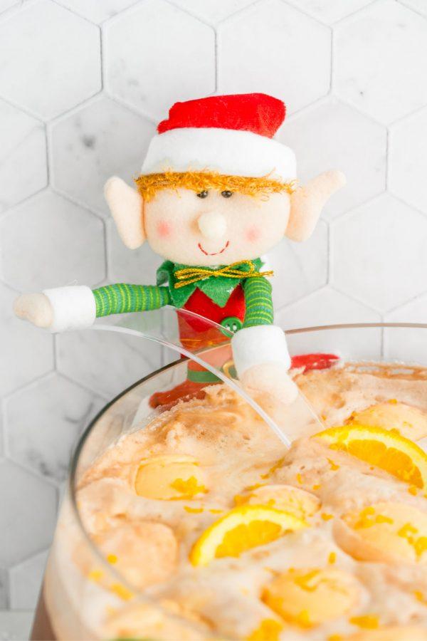 A cute stuffed elf getting a ladle full of Christmas Punch.