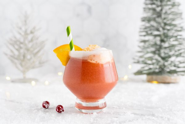 The finished Christmas Punch recipe in a glass garnished with a paper straw and an orange slice.