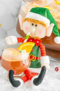A cute stuffed elf sipping on a glass of non-alcoholic Christmas Punch.