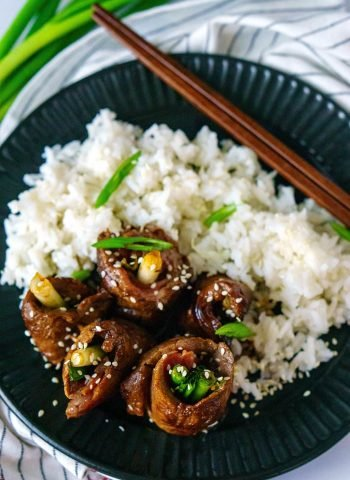 Overhead picture of beef rolls on a black plate with rice.