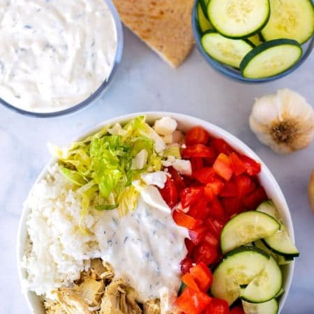 Gyro bowl with rice, slow cooker chicken, tomatoes, bell pepper, cucumber, shredded lettuce, feta, and pita triangles.