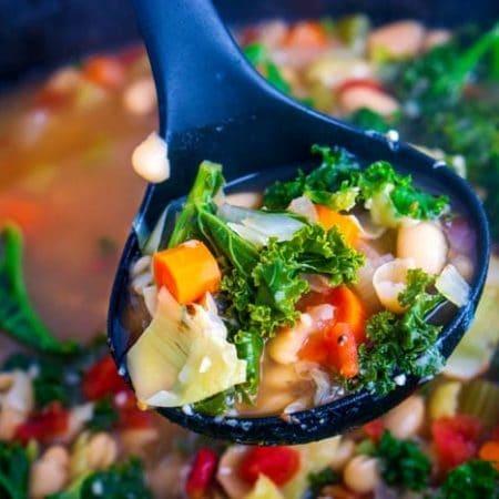 A ladle full of hot soup.