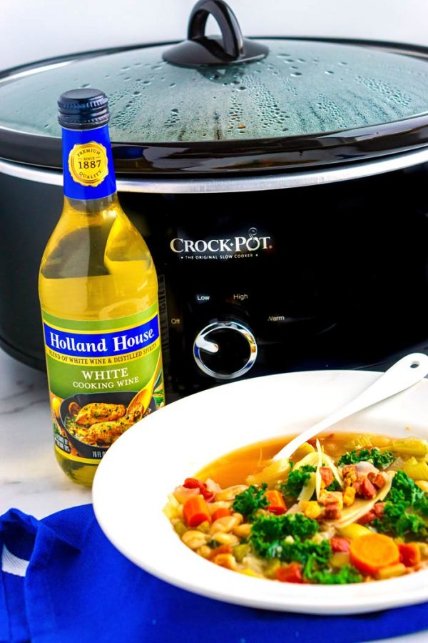 A bowl of soup with a Crock-Pot in the background.