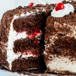 A close up picture of a slice of black forest cake being taken from the larger cake.