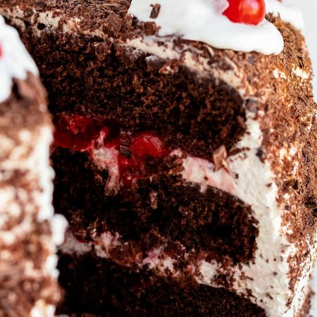 A close up picture of a slice of black forest cherry cake.