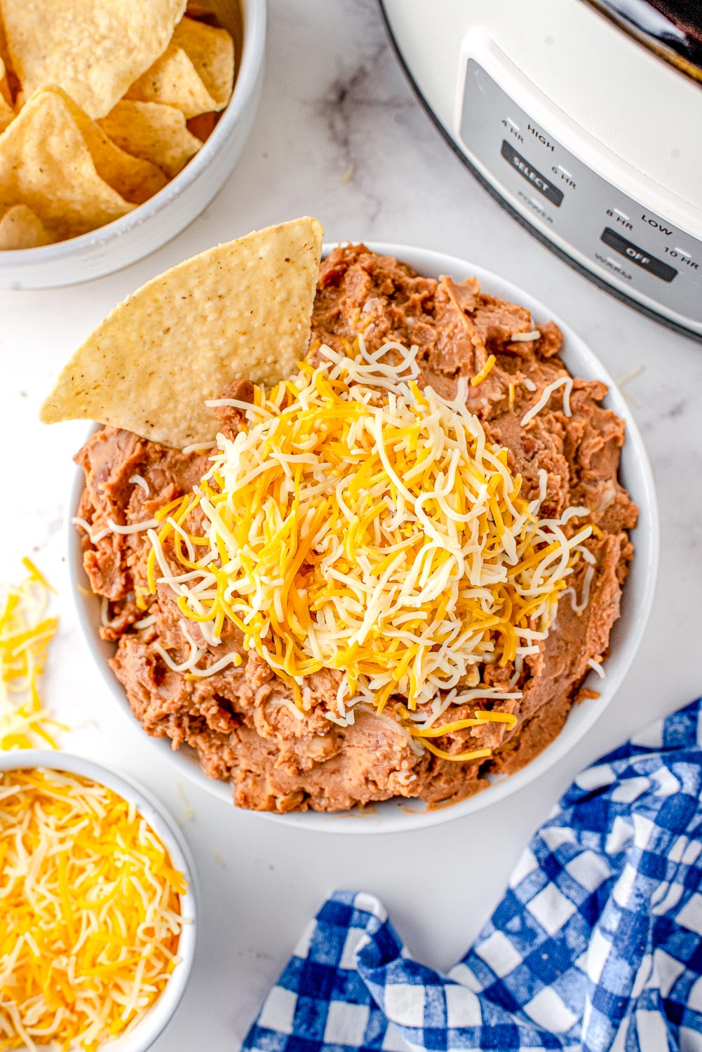 An overhead picture of the finished Mexican Refried Beans in a white bowl that's garnished with shredded Mexican cheese and tortilla chips.