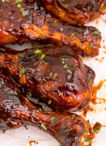 A close up picture of Baked BBQ Chicken Drumsticks on parchment paper.