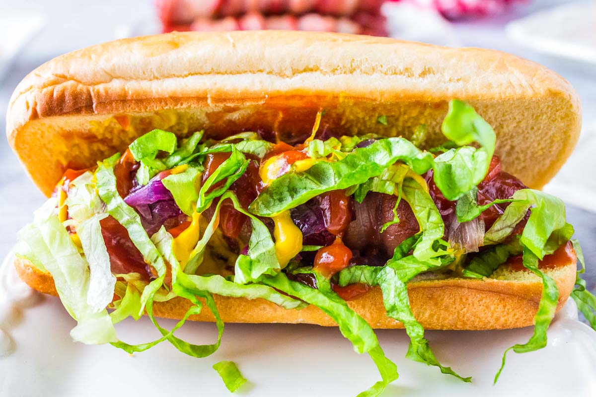 A close up picture of a Bacon Wrapped Hot Dog covered in ketchup, mustard, onions, and lettuce.