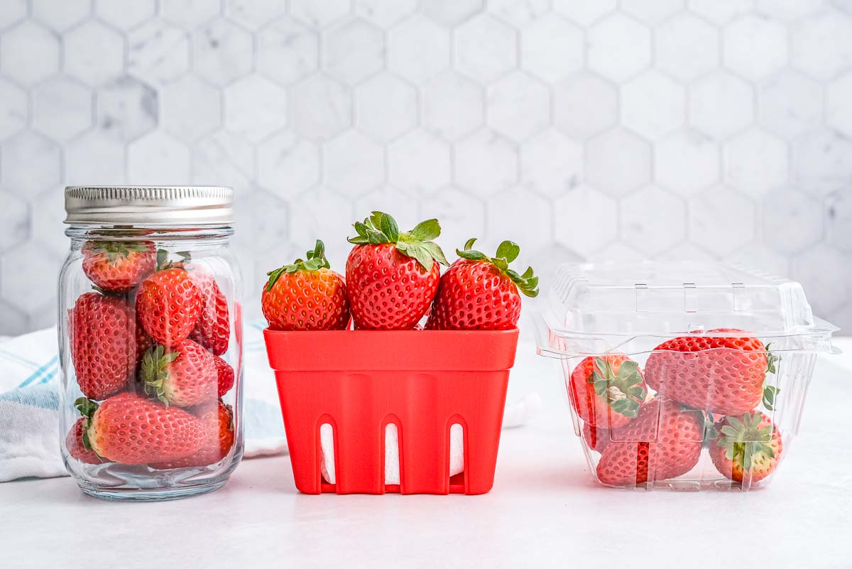 Strawberries stored 3 differnt ways: in their original container, in an open container, and in a glass jar.