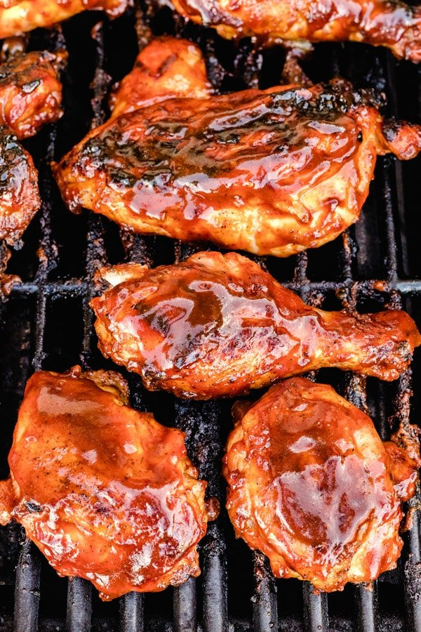 A close up picture of grilled BBQ chicken on the grill.
