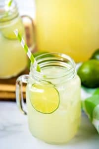 Limemade in a glass jar with a lime and paper straw.