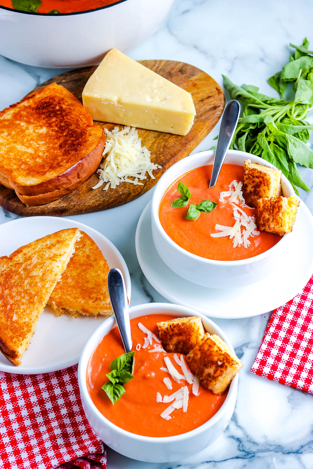 Two bowls of homemade tomato soup with grilled cheese sandwiches.