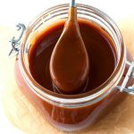 A spoon getting a scoop of caramel sauce that's in a storage jar.