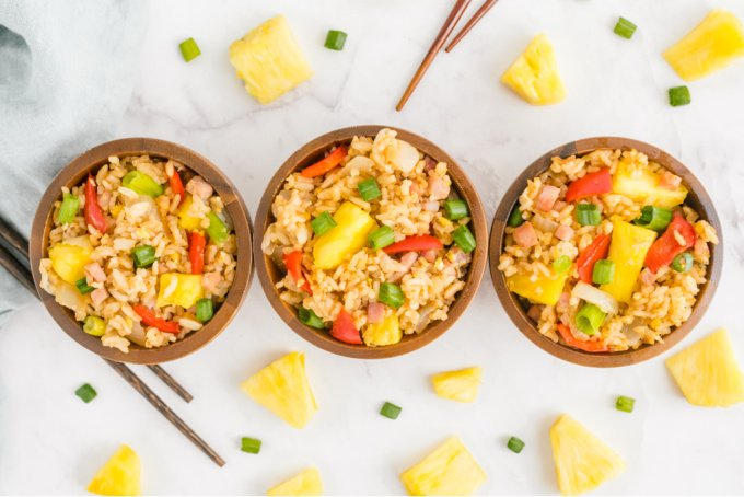 Hawaiian Fried Rice in three wooden bowls with chopsticks.