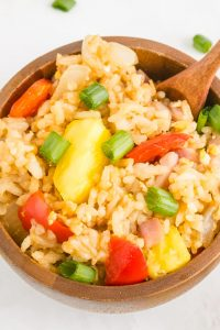A close up picture of Hawaiian Fried Rice in a wooden bowl.
