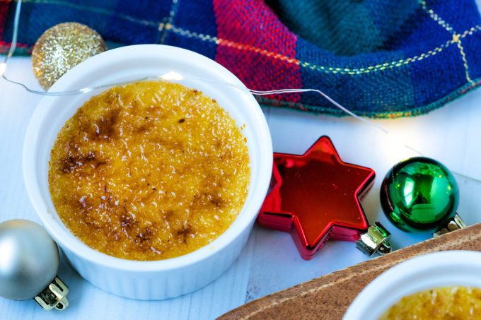 A dish of creme brulee with Christmas ornaments around it.