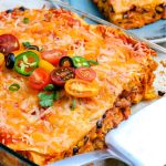 The chicken enchilada casserole inside the baking dish with a few slices taken out of it.