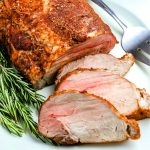 The cooked pork loin on a plate along with 3 slices of the pork.