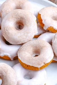 An overhead picture of a pile of glazed pumpkin donuts.