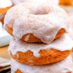 A close up picture of a stack of pumpkin donuts.